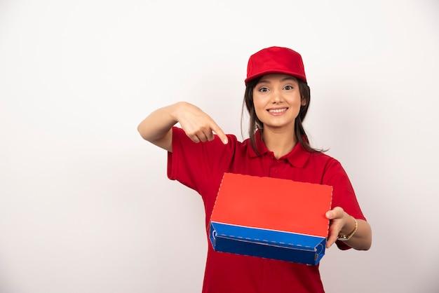 Junge lächelnde frau in der roten uniform, die pizza im kasten liefert.