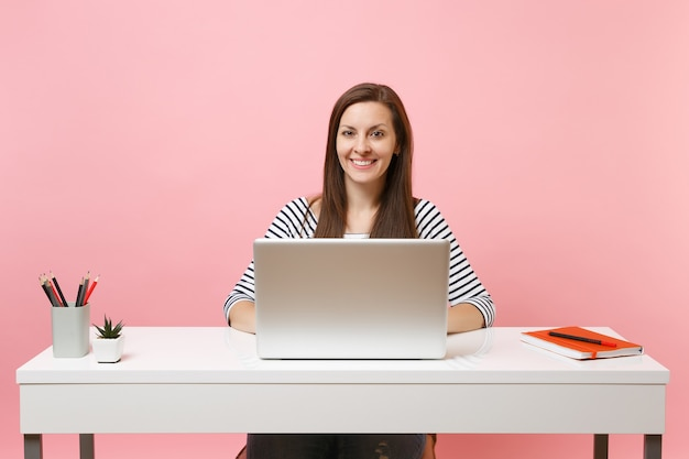 Junge lächelnde frau in freizeitkleidung, die mit laptop an einem projekt arbeitet, während sie im büro sitzt