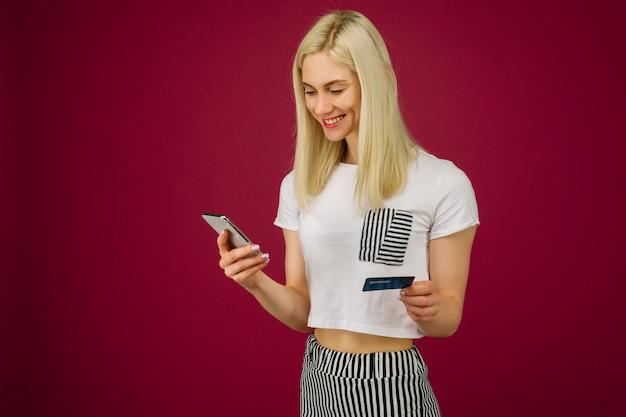 Junge lächelnde frau kauft online. hält ein smartphone und eine kreditkarte in der hand auf rubin