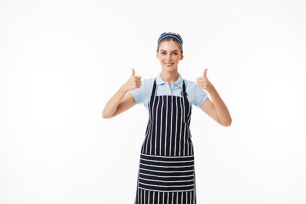Junge lächelnde frau kochen in gestreifter schürze und mütze glücklich