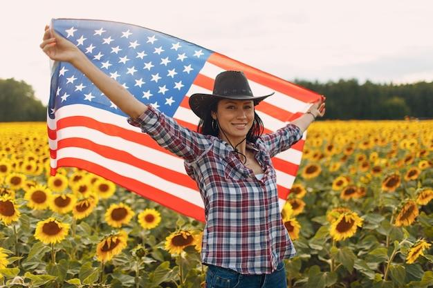 Junge lächelnde frau mit amerikanischer flagge im sonnenblumenfeld th des juli-unabhängigkeitstag-usa-konzepts