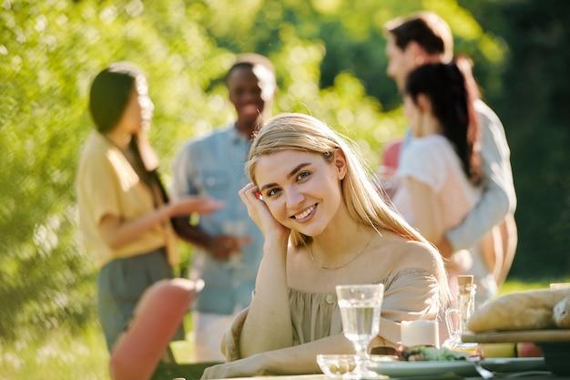 Junge lächelnde frau mit den langen blonden haaren, die sie beim sitzen durch bedienten tisch auf von den freunden betrachten betrachten