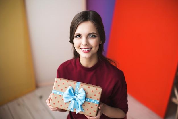 Junge lächelnde frau mit geschenk