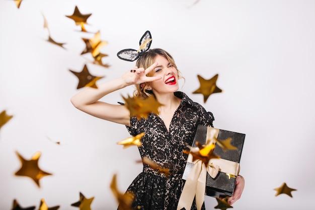 Junge lächelnde frau mit geschenkbox, die helles ereignis, geburtstagsfeier feiert, trägt elegantes schwarzes modekleid. funkelndes goldkonfetti, spaß haben, tanzen.