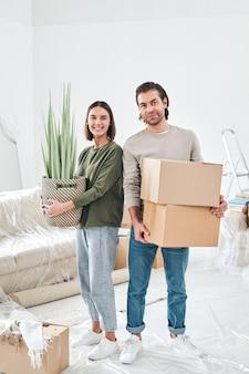Junge lächelnde frau mit grüner hauspflanze und ihrem ehemann mit zwei gepackten kisten, die im wohnzimmer ihres neuen hauses stehen