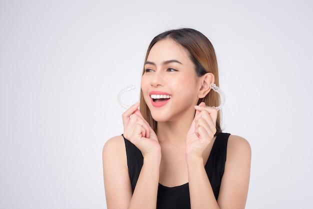 Junge lächelnde frau mit invisalign-klammern im studio, zahnmedizin und kieferorthopädisches konzept