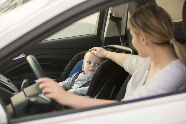 Junge lächelnde frau posiert mit ihrem baby im auto
