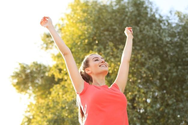 Junge lächelnde frau ruht sich nach einem aktiven fitnesstraining im park aus.
