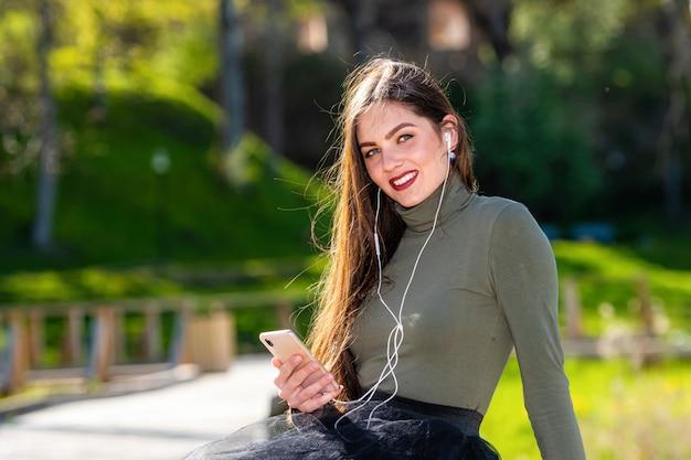 Junge lächelnde frau sitzt auf bank im park im freien, die musik mit kopfhörern unter verwendung des mobiltelefons an einem sonnigen und windigen tag hört