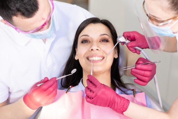 Junge lächelnde frau sitzt auf dem zahnarztstuhl mit zwei arbeitenden ärzten