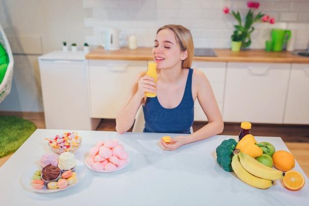 Junge lächelnde frau trinkt entgiftungswasser, während sie zwischen gesundem und ungesundem essen in der weißen küche wählt. schwierige wahl zwischen frischem obst, gemüse oder süßigkeiten. diät halten. diät. gesundes essen