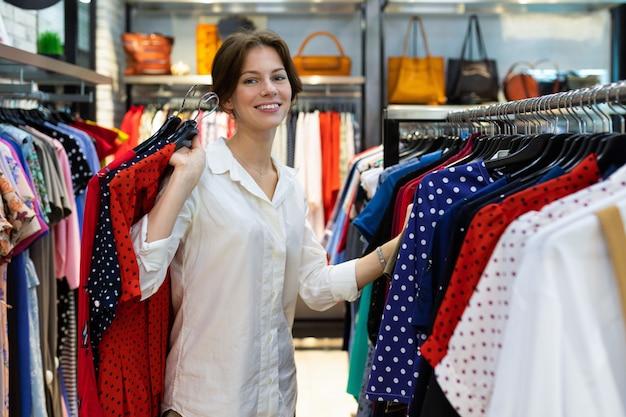 Junge lächelnde frau wählt kleid und hält gepunktete kleider im laden