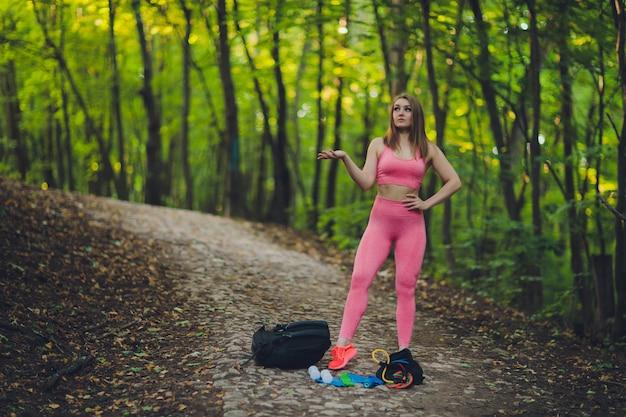 Junge lächelnde frau wanderer, die bergpfad wandert, auf grasbewachsenem hügel gehend, rucksack tragend. outdoor-aktivität, tourismuskonzept.