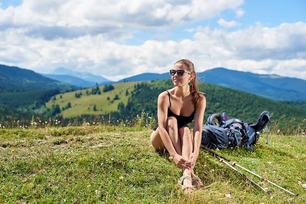 Junge lächelnde frau wanderer, die im karpatengebirgspfad wandert, auf grasbewachsenem hügel mit trekkingstöcken und rucksack sitzend genießt sommertag. outdoor-aktivität, tourismuskonzept