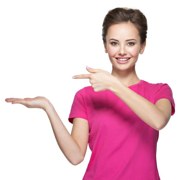Junge lächelnde frau zeigt mit dem finger auf handfläche