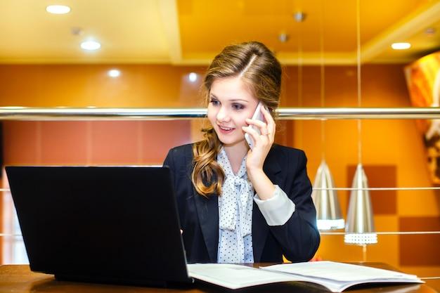 Junge lächelnde frauen, die in einem café mit einem laptop sitzen und am handy sprechen