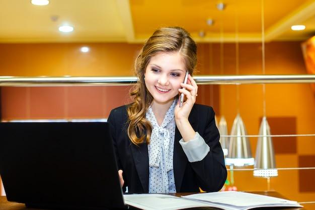 Junge lächelnde frauen, die in einem café mit einem pc-notizbuch sitzen und am handy sprechen