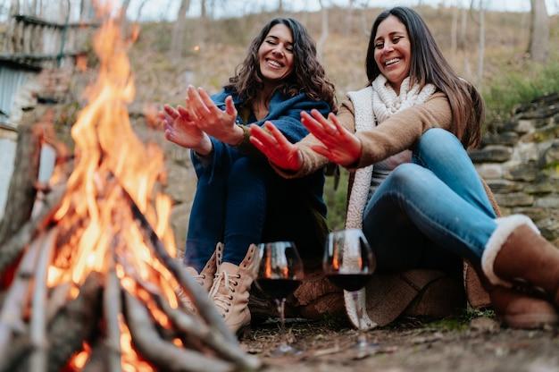 Junge lächelnde frauen, die sich neben dem feuer erwärmen. gläser rotwein. lagerfeuer, aktivitäten im freien, entspannung, zusammengehörigkeitskonzept.