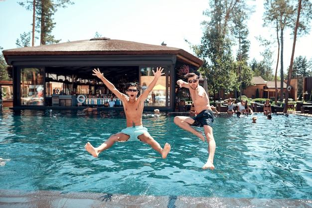 Junge lächelnde freunde, die in swimmingpool springen