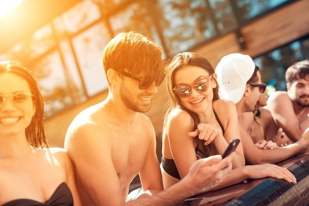 Junge lächelnde freunde, die smartphone am poolside verwenden