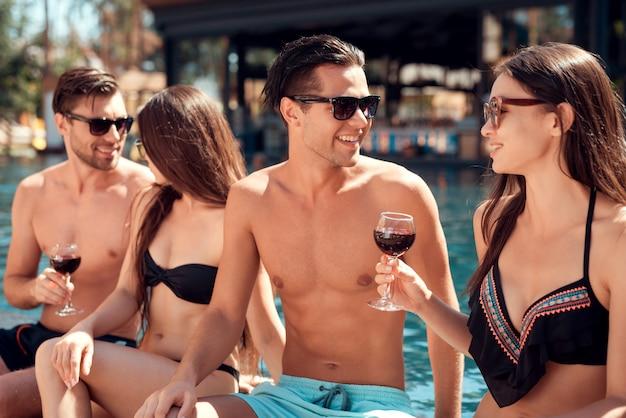 Junge lächelnde freunde, die wein am poolside trinken