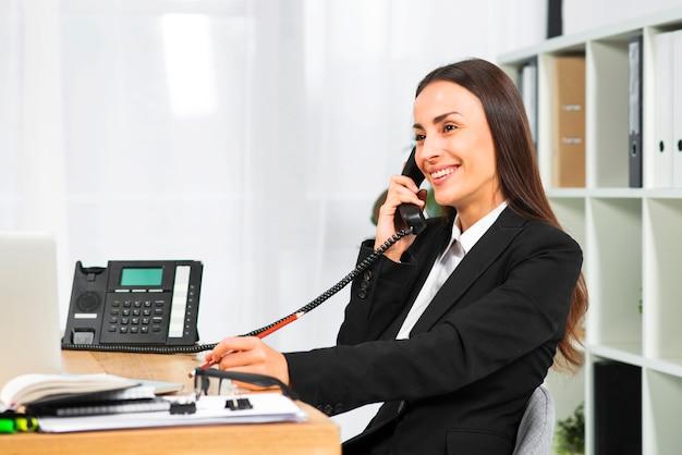 Junge lächelnde geschäftsfrau bei der unterhaltung am telefon im büro