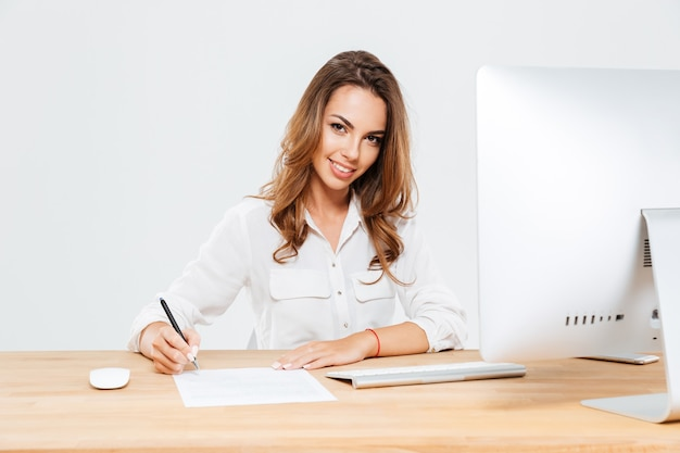 Junge lächelnde geschäftsfrau, die dokumente unterschreibt, während sie am schreibtisch sitzt