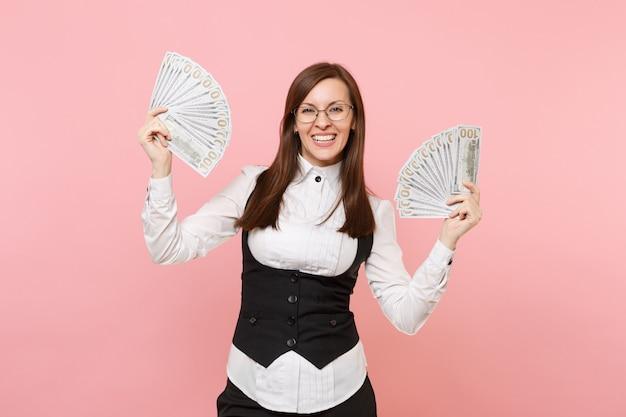Junge lächelnde geschäftsfrau in den gläsern, die bündel viele dollar, bargeld halten und hände einzeln auf rosafarbenem hintergrund ausbreiten. chefin. erfolg karriere reichtum. kopieren sie platz für werbung.