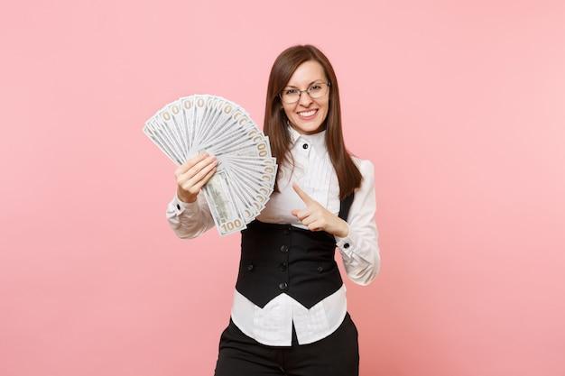 Junge lächelnde geschäftsfrau in gläsern, die mit dem zeigefinger auf bündel viele dollar zeigen, bargeld einzeln auf rosafarbenem hintergrund. chefin. erfolg karriere reichtum. kopieren sie platz für werbung.
