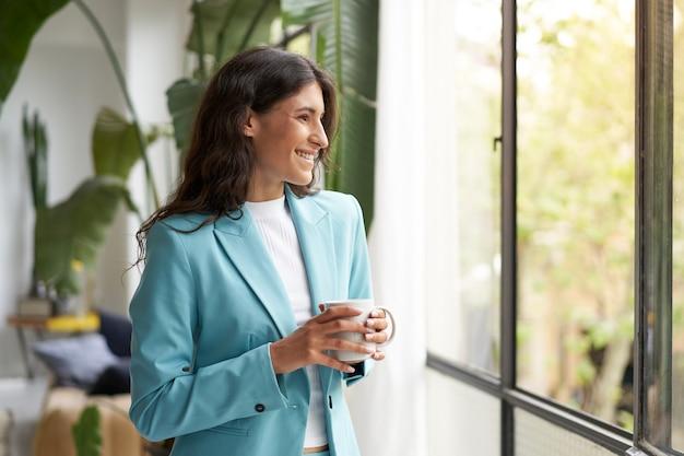 Junge lächelnde geschäftsfrau zufrieden mit einer gut gemachten arbeit, die sich mit ihrem morgenkaffee oder -tee entspannt ...