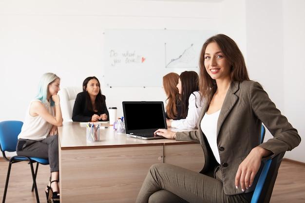 Junge lächelnde geschäftsfrauen, die neues projekt im büro bearbeiten.