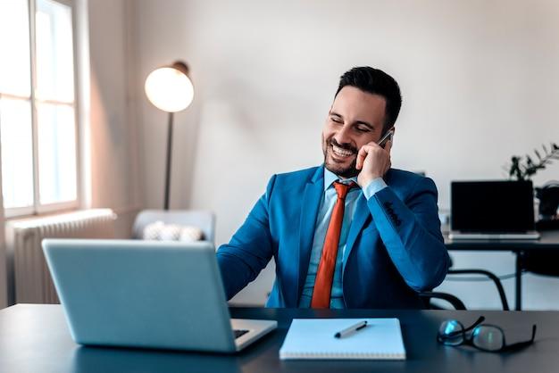 Junge lächelnde geschäftsmänner, die in seinem büro arbeiten und an seinem handy sprechen.