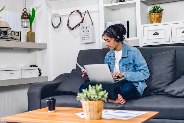 Junge lächelnde glückliche frau, die sich mit laptop-computer entspannt und arbeitet