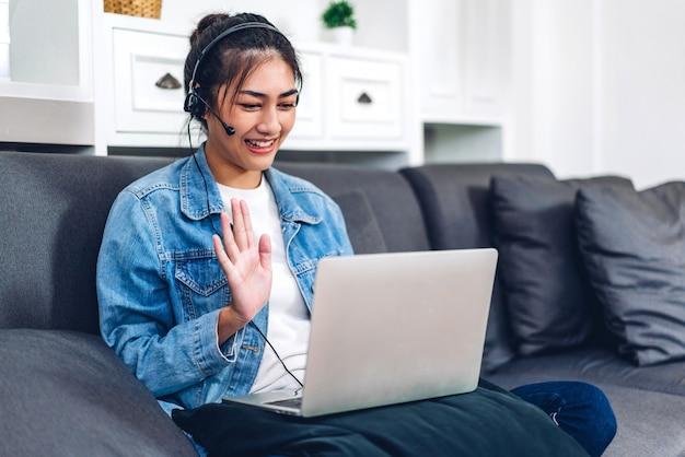 Junge lächelnde glückliche schöne asiatische frau, die unter verwendung der laptop-computerarbeit und videokonferenzbesprechung zu hause entspannt