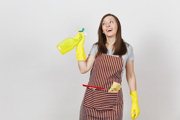 Junge lächelnde hausfrau in gelben handschuhen, gestreifter schürze, putzlappen, rakel in der tasche isoliert