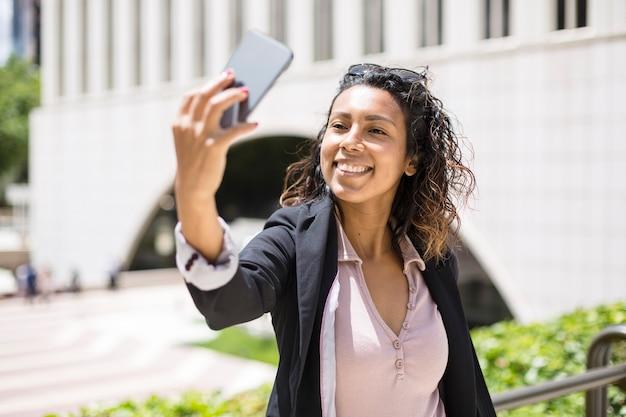 Junge lächelnde hispanische amerikanerin, die mit ihrem smartphone ein selfie im freien macht. platz für text.