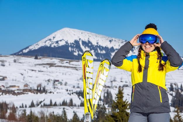 Junge lächelnde hübsche frau, die ski hält. berge im hintergrund. winterreisen. platz kopieren