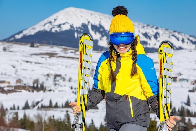Junge lächelnde hübsche frau, die ski hält. berge im hintergrund. winterreisen