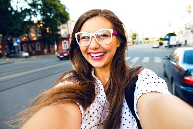 Junge lächelnde jugendlich glückliche frau, die selfie auf der straße macht, ling haare, helles make-up und niedliche klare brille, allein reisend, spaß, positive stimmung, freude, urlaub machend