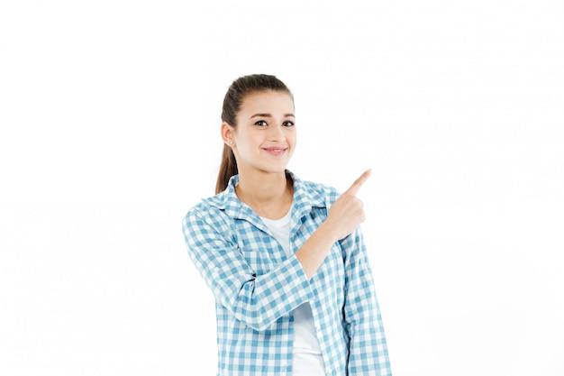 Junge lächelnde junge frau, die am kopienraum zeigt