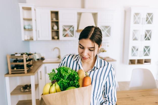 Junge lächelnde kaukasische frau halten öko-einkaufstasche mit frischem gemüse und baguette in der modernen küche.