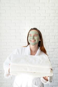 Junge lächelnde kaukasische frau mit einer gesichtsmaske, die bademäntel hält, die einen stapel weiße badetücher halten