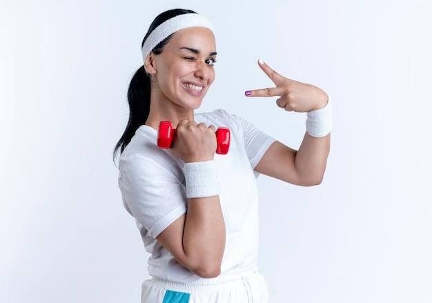 Junge lächelnde kaukasische sportliche frau, die stirnband und armbänder trägt, blinzelt auge, das hantel und gestikulierendes siegeshandzeichen lokalisiert auf weißem raum mit kopienraum hält