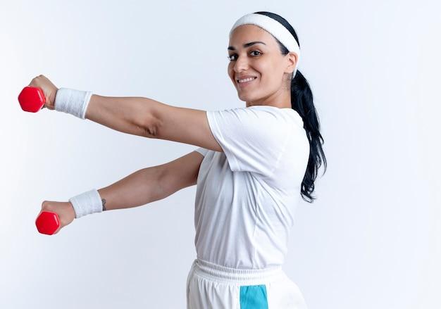 Junge lächelnde kaukasische sportliche frau, die stirnband und armbänder trägt, steht seitlich mit hanteln, die auf weißem raum mit kopienraum isoliert werden