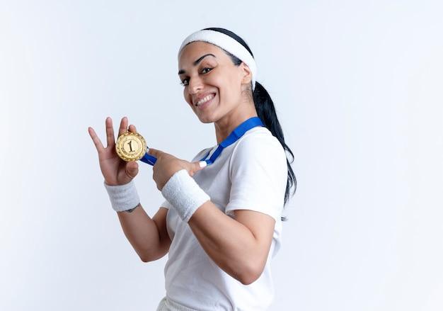 Junge lächelnde kaukasische sportliche frau steht seitlich und hält und zeigt auf goldmedaille