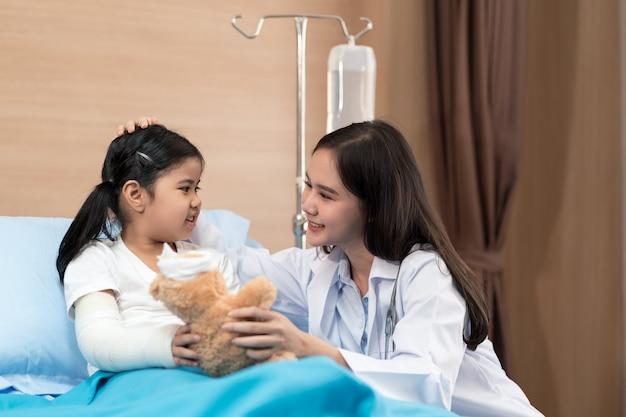 Junge lächelnde kinderärztin und kinderpatientin mit teddybär im gesundheitszentrum