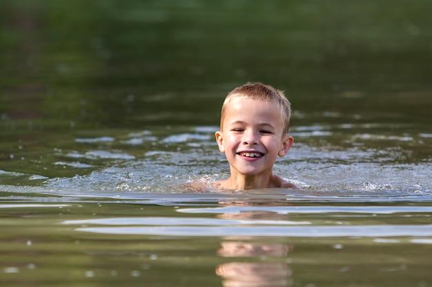 Junge lächelnde kinderjungenschwimmen im schlammigen wasser