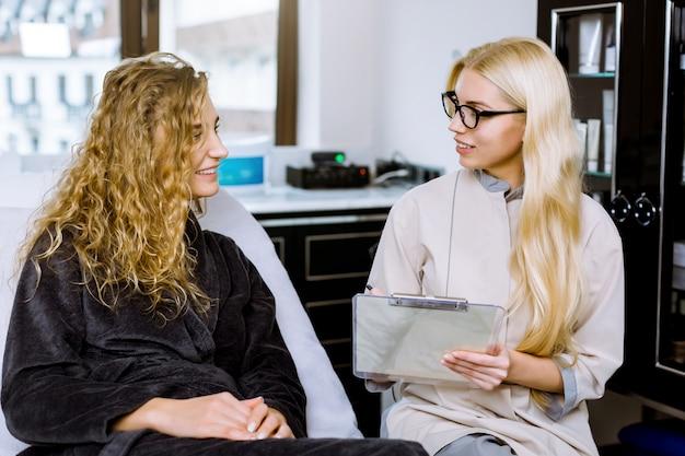 Junge lächelnde kosmetikerin in schwarzen gläsern, die informationen über neue kosmetik- und schönheitsprodukte zum kunden, hübsche blonde frau im grauen bademantel zeigen