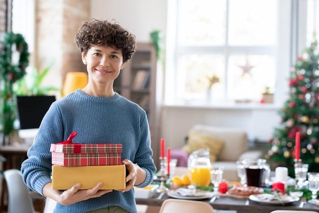 Junge lächelnde, lockige brünette frau, die geschenkboxen mit geschenken für ihre familie hält, während sie gegen einen geschmückten weihnachtsbaum und einen servierten tisch steht