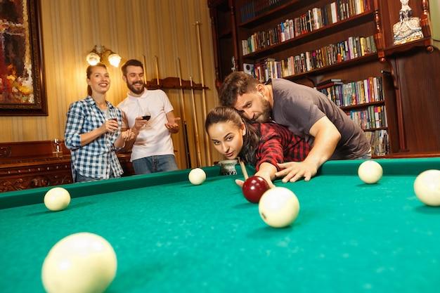 Junge lächelnde männer und frauen, die nach der arbeit billard im büro oder zu hause spielen. geschäftskollegen, die sich mit freizeitaktivitäten beschäftigen